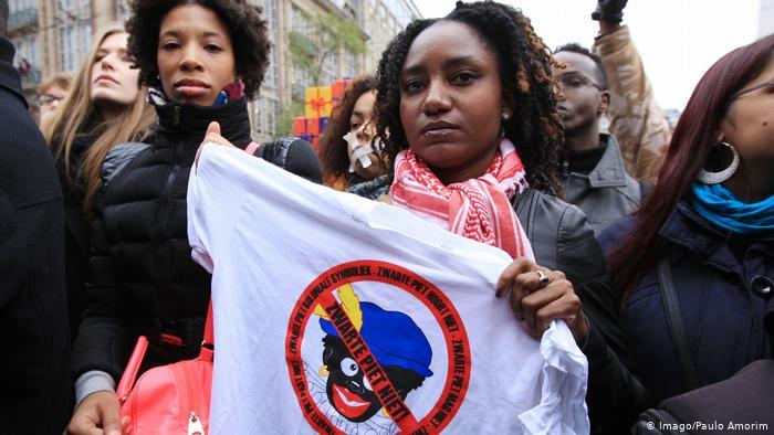 Una persona negra sujeta una camiseta con la señal de prohibido el blackface